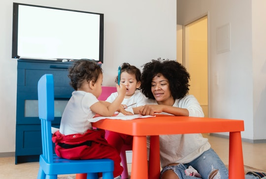 mom and twin toddlers sitting at toddler table