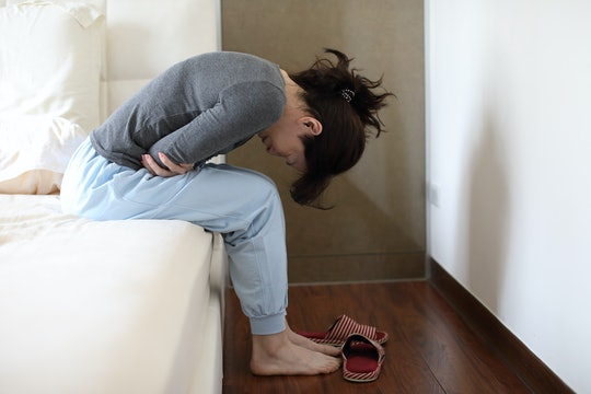 woman with cramps sitting on edge of bed