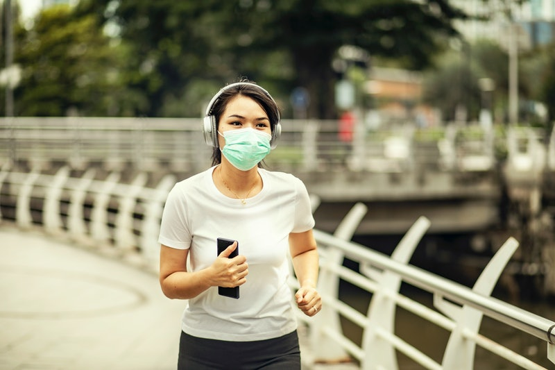 A person jogs outside with a mask on. You can exercise outside safely during the pandemic, as long a...
