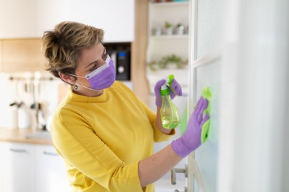 A woman cleans her house. A person with COVID-19 should wear masks inside as well as outside to prevent spreading it to other members of the household.