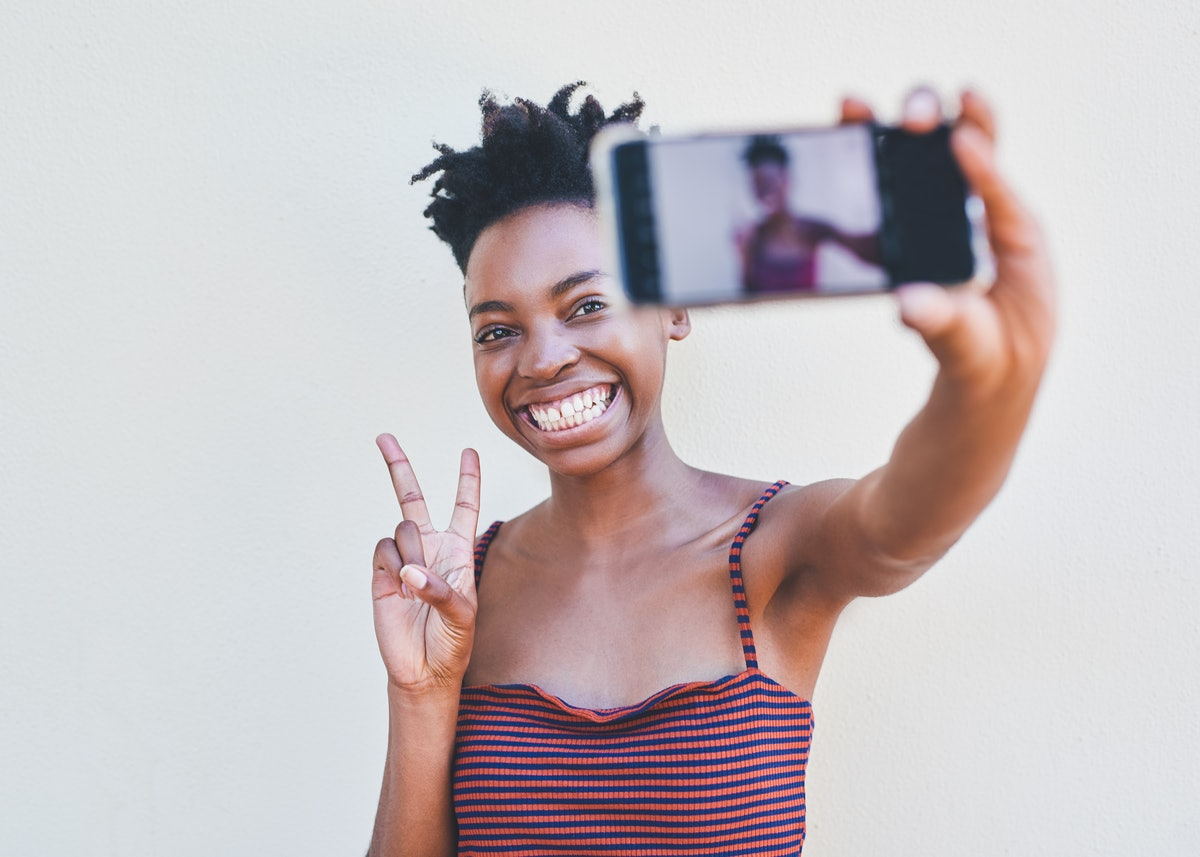 A young woman poses for a selfie in front of a white wall in the middle of summer.