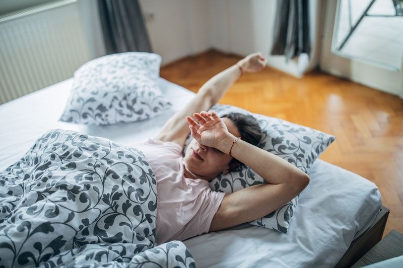 A person wearing a nightshirt and robe sits up in bed, stretching. If you're having trouble getting out of bed during COVID-19, you can still get in exercises that will help you feel a bit better.