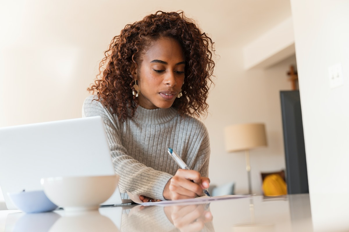 A young woman sits at her kitchen table with her laptop and jots things down on a piece of paper.
