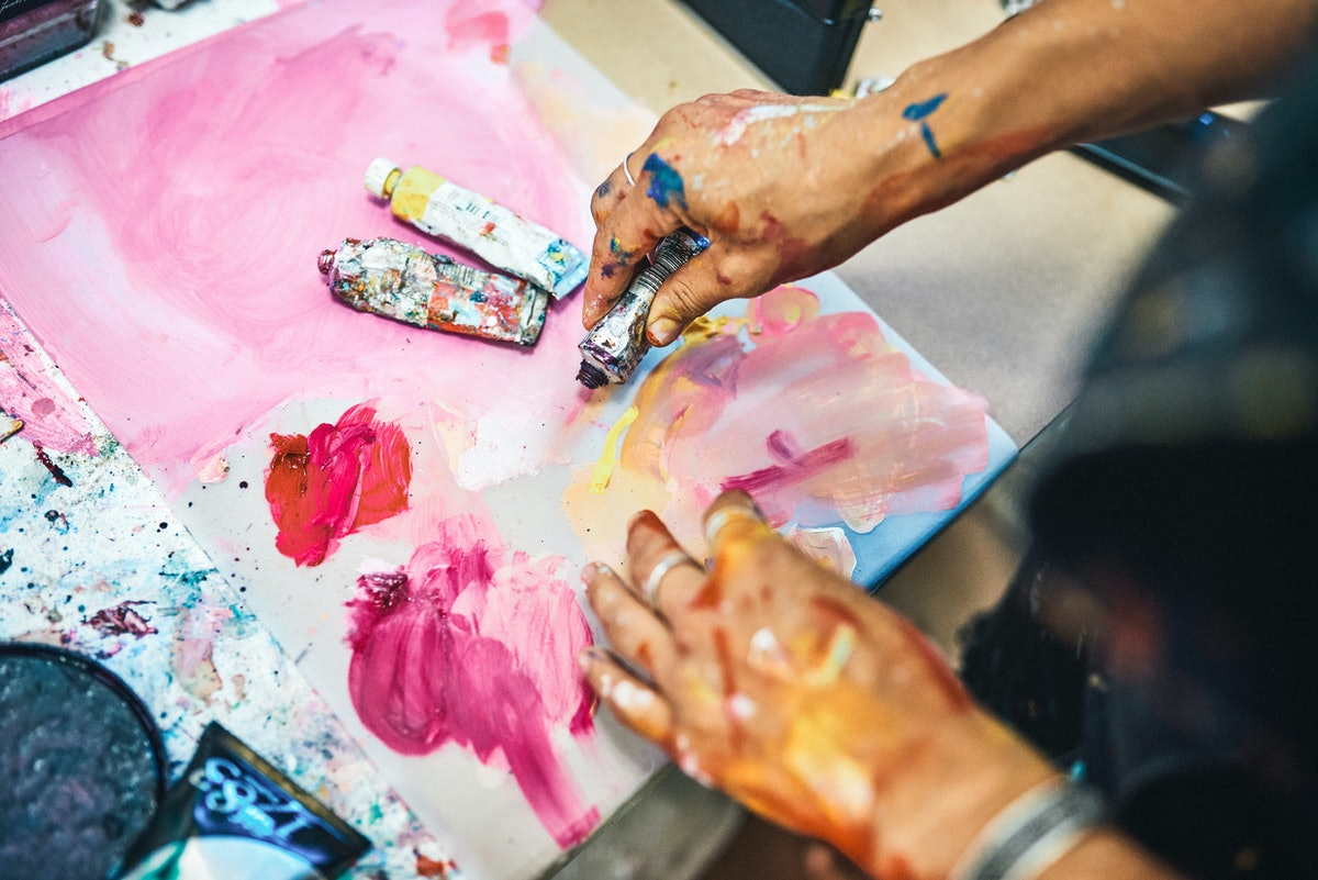 A young woman plays with watercolor paints on a paint-splattered table.