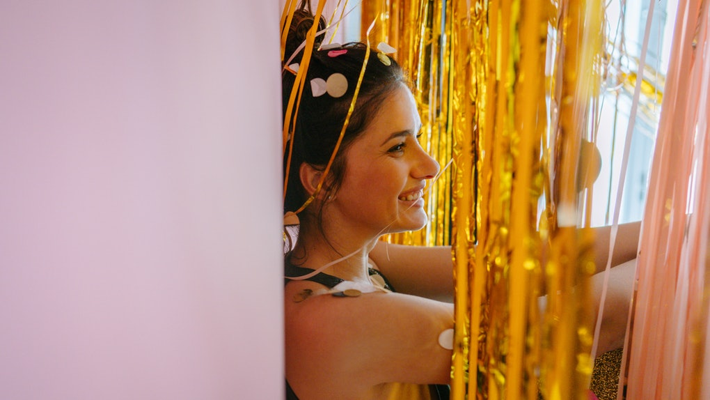 A young woman poses against a pink wall amongst gold streamers and confetti.