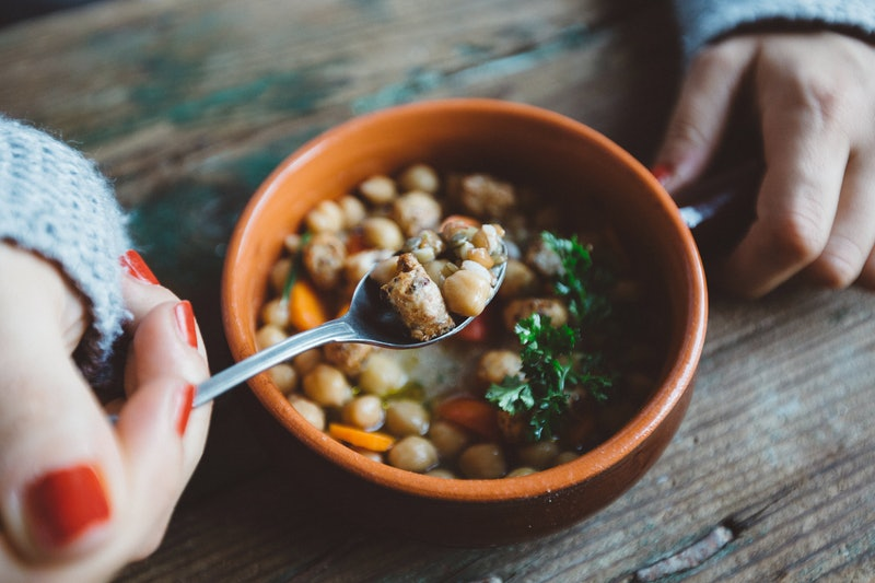 A woman eats beans in quarantine. Social distancing's effect on your gut health has to do with what you eat, your schedule, and your stress levels.