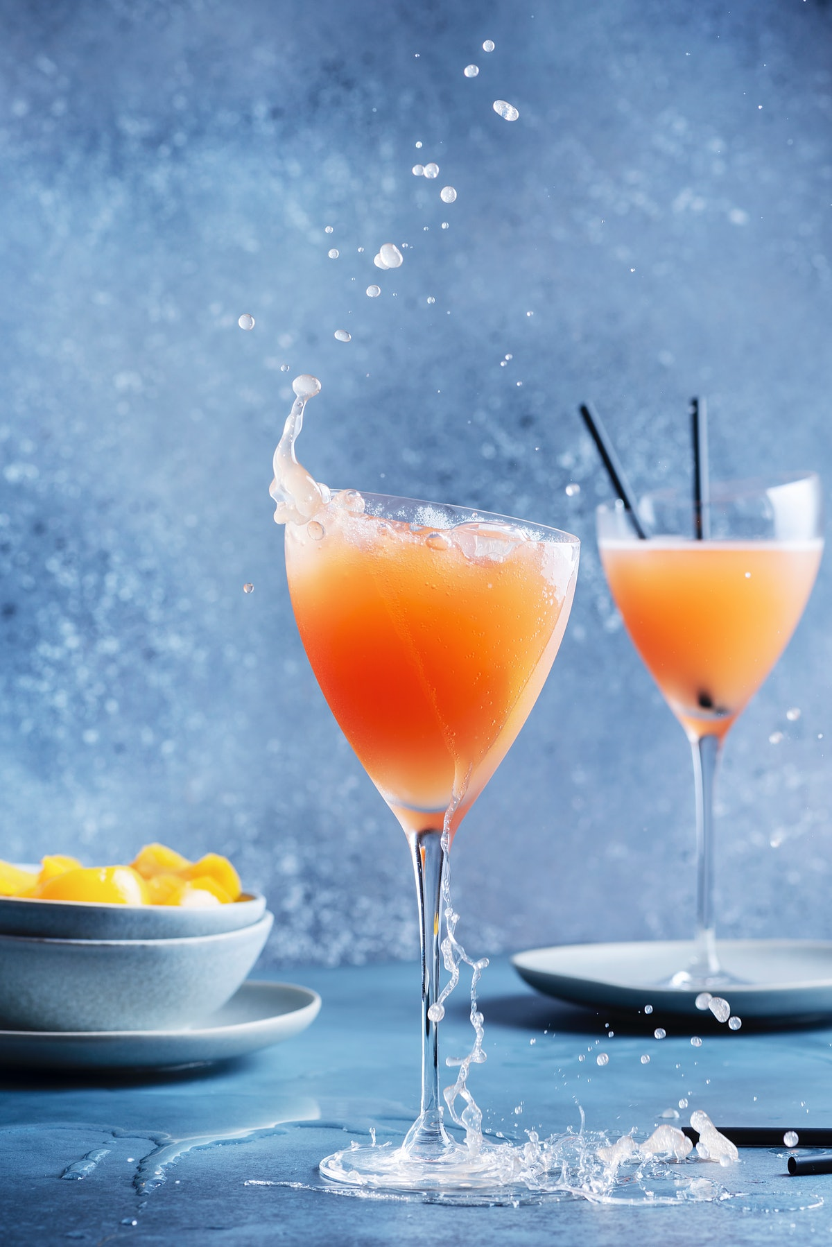 Two bellinis are places on a table with a bowl of peaches next to them.