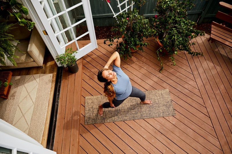A woman does yoga on her patio. According to science, time is slowing down during quarantine.