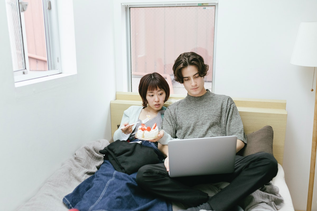 A young couple lays in bed and tries to do a virtual escape room on their laptop.