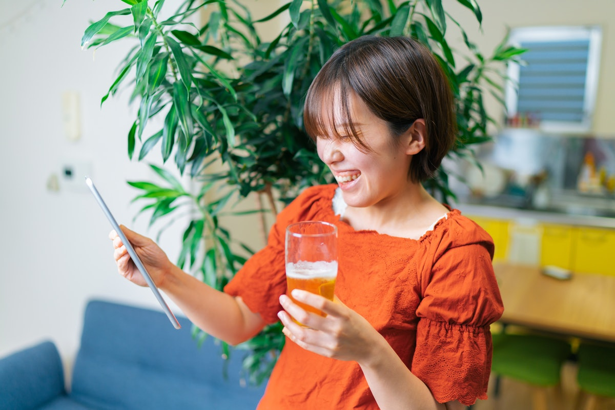 A young woman laughs while holding a drink and video chatting on her tablet.