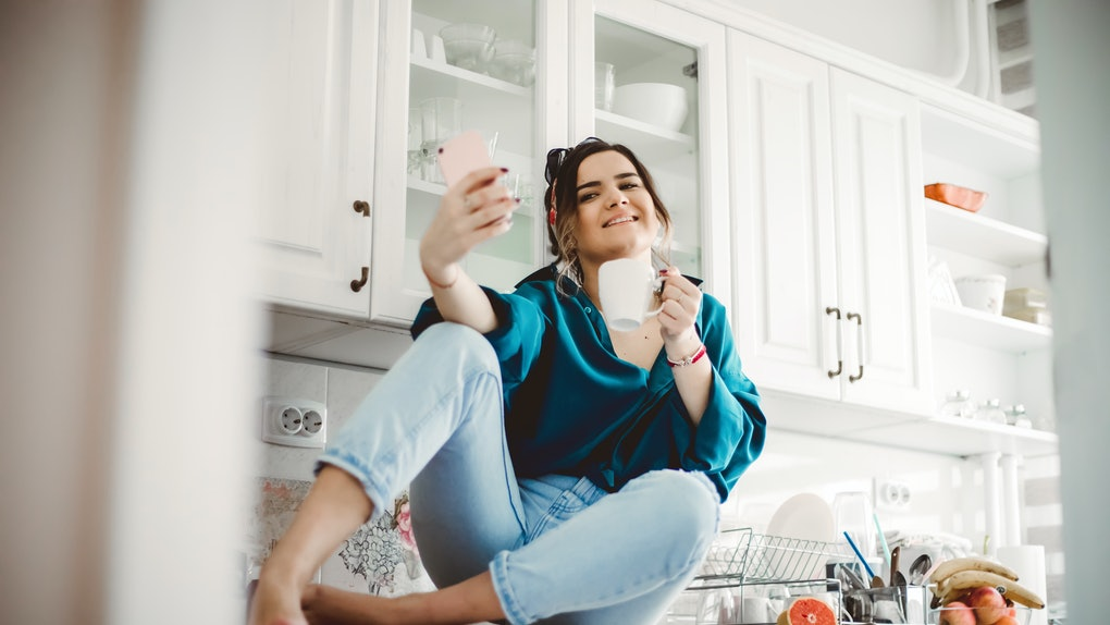 A young woman sits on her kitchen counter with a cup of coffee and takes a selfie on her phone.
