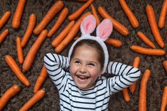 little girl wearing bunny ears with carrots in easter photo booth
