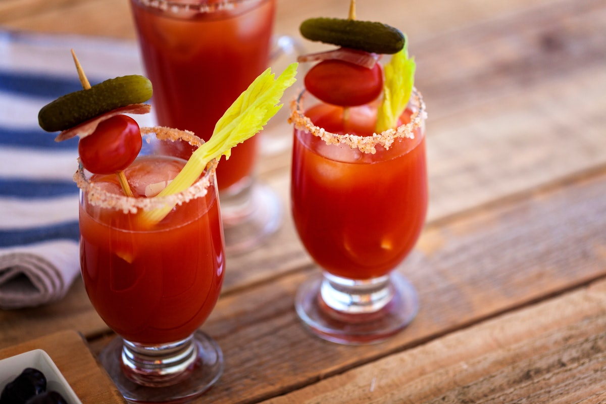 Two Bloody Marys placed on a picnic table have sticks of celery, and skewers of tomato, bacon, and small pickles sticking out of them.