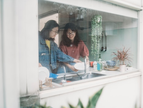 Two women cook inside their kitchen as seen from the outside of their house. What happens to your body when you spend too much time inside?