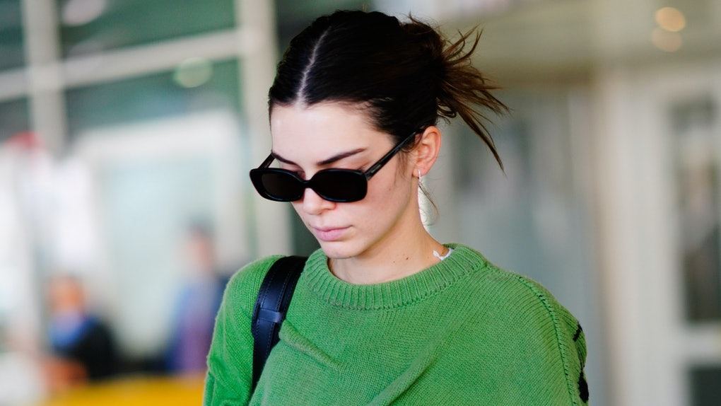 Kendall Jenner steps out in a green sweater and black shades.