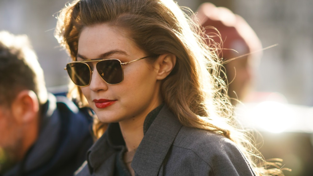 Gigi Hadid hits the streets in a gray blazer and aviator sunglasses.