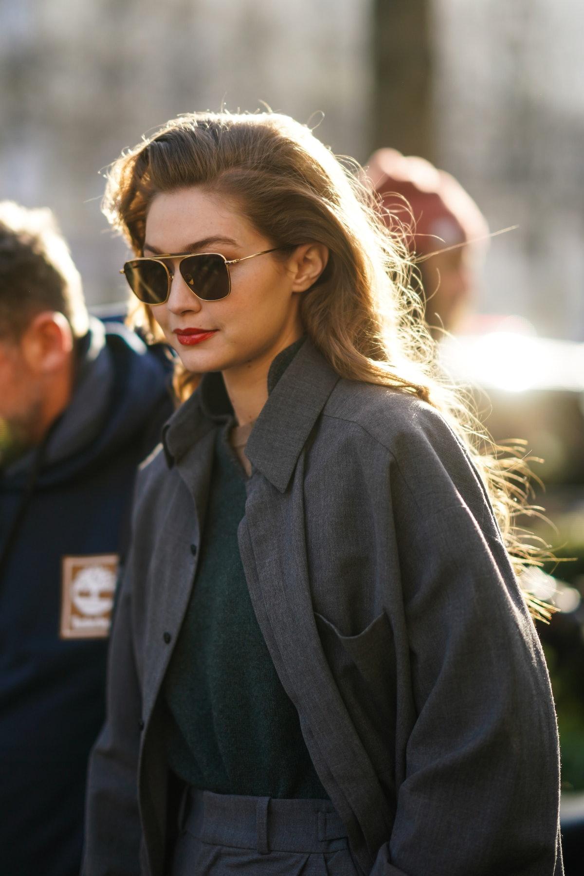 Gigi Hadid hits the streets in a gray blazer and aviator sunglasses.