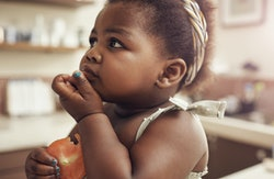baby eating tomato
