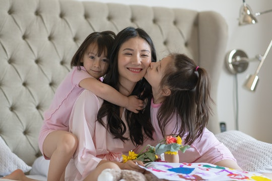 mother and two daughters on mother's day in bed