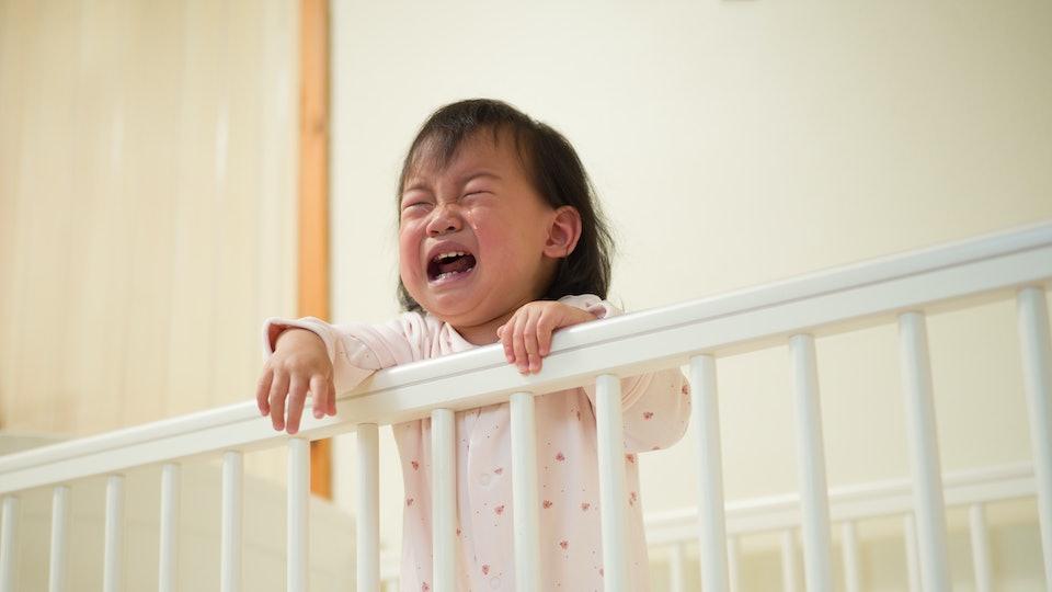 toddler girl crying in crib