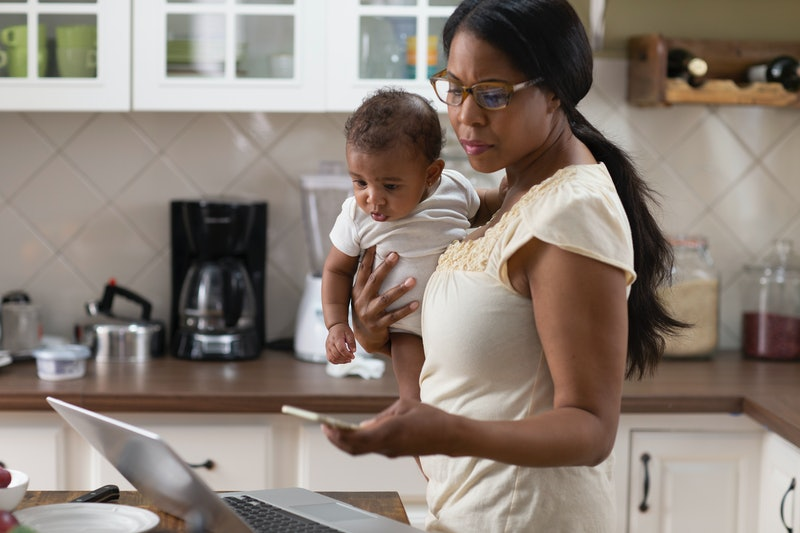 Woman working from home with a newborn during coronavirus. Isolation and stress can make burnout likely for people working from home right now.