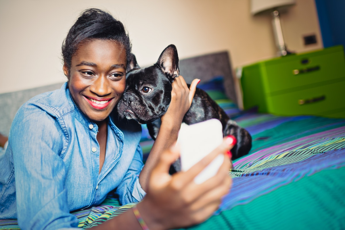 A young woman poses for a selfie with her puppy on a colorful bed.