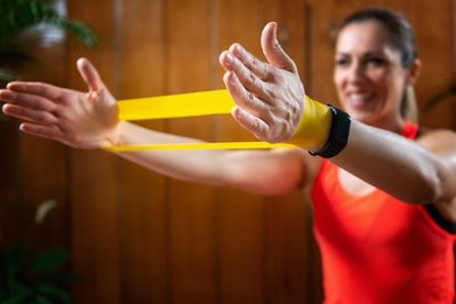 A person uses a yellow resistance band to exercise her traps and upper lats. Banded pull aparts are one of the most effective resistance band exercises for building strength and stability.