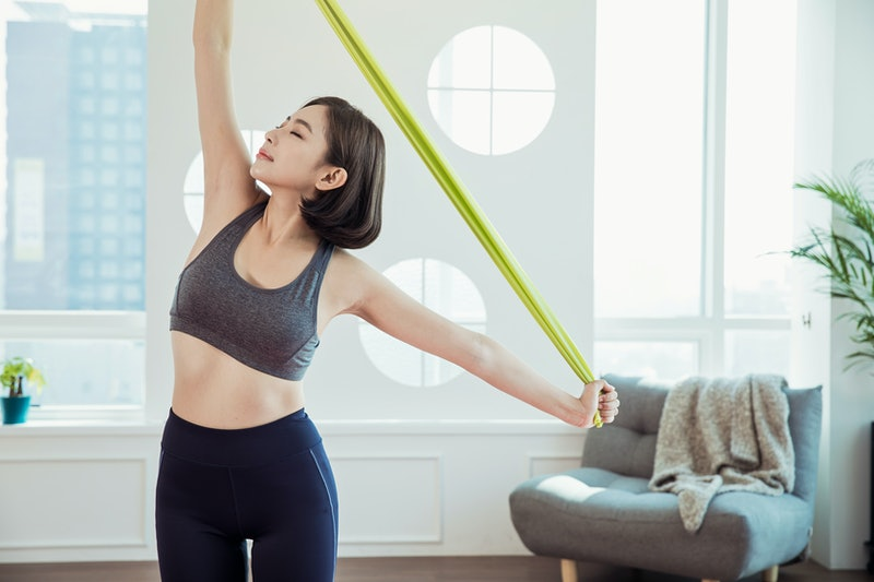 A person holds a behind-the-back resistance band stretch. Resistance band workouts are excellent for building strength, increasing flexibility, and maintaining muscle mass.