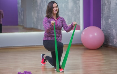 A person performs a half-kneeling bicep curl with a resistance band. You can workout at home to benefit every part of your body with only resistance bands.