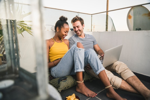 A young couple laughs on their apartment's roof while video chatting on their laptop.