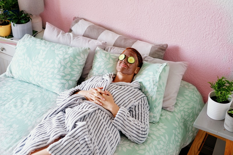 A woman in a bathrobe does a facemask, with cucumber slices over her eyes. Consider these reasons you should stop showering every day a form of self care.