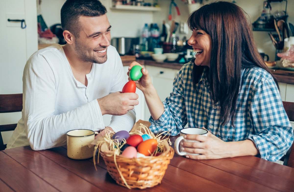 A young couple smiles at each other while holding their painted Easter eggs.
