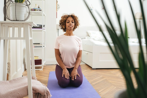 A young woman meditates while doing yoga on a purple mat in her home.