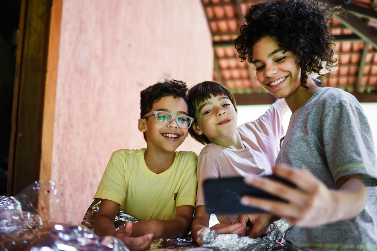 A woman takes a selfie with her two younger siblings on Easter Sunday.