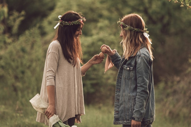 Two friends in flower crowns hold up Easter eggs in a field on a sunny day.