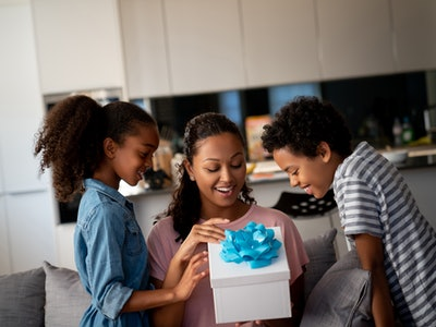 a mom opening a mother's day gift from her two kids
