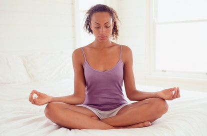A woman sits on her bed meditating, one way to fall back asleep after waking up.