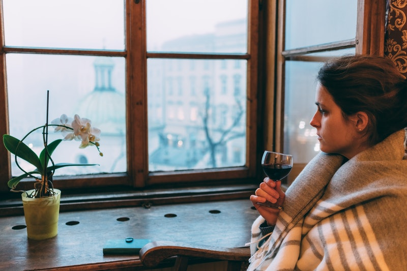 A woman drinks wine alone at home while staring at her cactus. What happens to your brain when you drink alcohol? Experts explain.