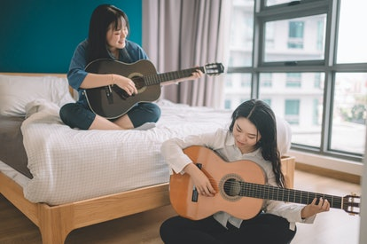 Two women play guitar in their apartment. Music and other art forms can be therapeutic.