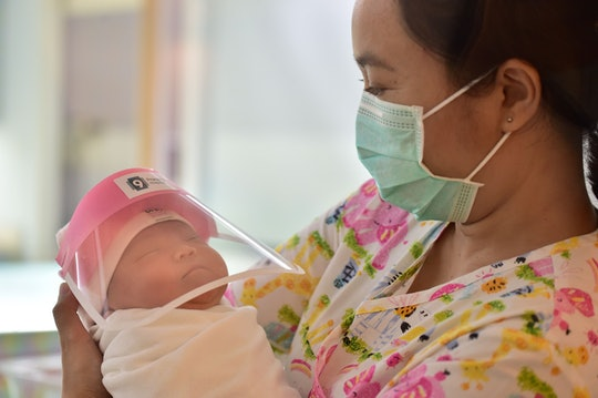 A staffer at a hospital in Thailand holds a newborn wearing a mini face shield to protect them against the novel coronavirus.
