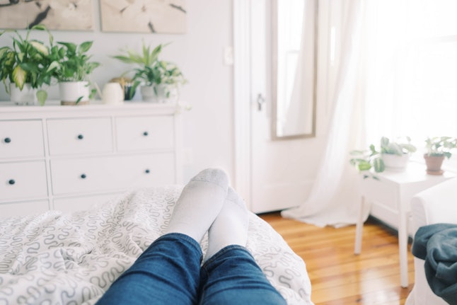 A person lies on a bed surrounded by houseplants. Indoor plants and gardening can give the same benefits for mental health as outdoor gardening, studies say.