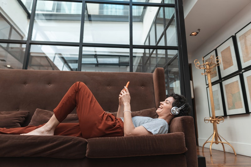 A woman with headphones watches Instagram live while lying on a brown velvet couch. Social distancin...