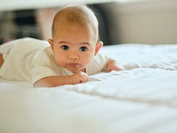cute baby tummy time on bed