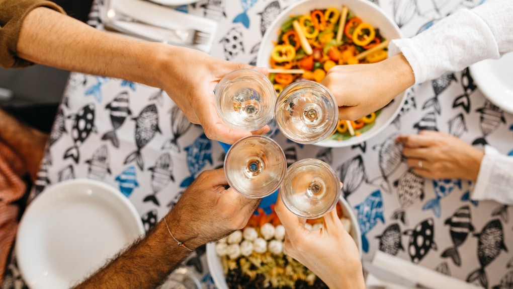 A family clinks their wine glasses together while having a dinner on Mother's Day.