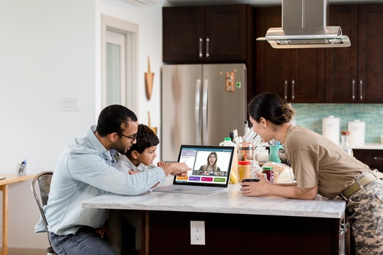 family in kitchen having a distance learning session on computer with teacher