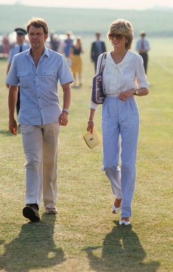 Princess Diana wearing white blouse and blue trousers.