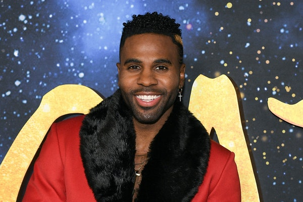 Jason Derulo smiles in front of a 'Cats' backdrop while wearing a red coat.