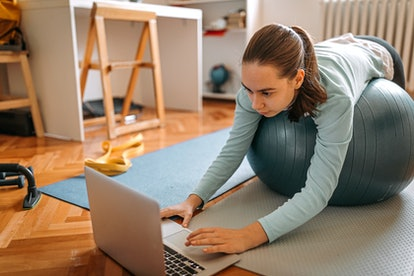 A person leans on her Swiss exercise ball while searching for a workout on her computer. Exercising while you have quarantine fatigue can be difficult, so take victories where you can get them.