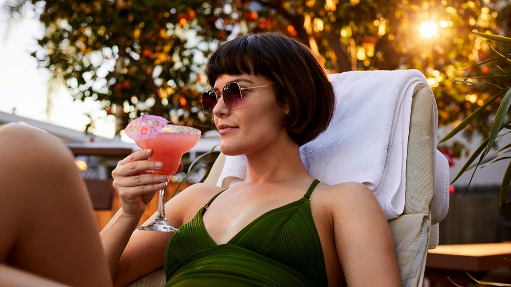 A young woman sits in a beach chair at sunset and drinks a frozen margarita.