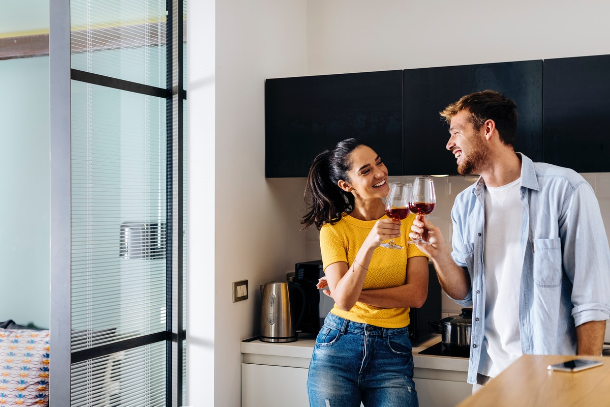 A young couple laughs in their kitchen while clinking their glasses of red wine.